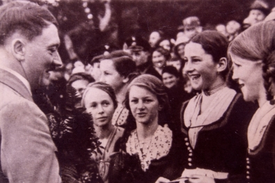 Adolf Hitler talking to young girls during a meeting with his su
