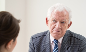 Aged unhappy interviewer on job conversation